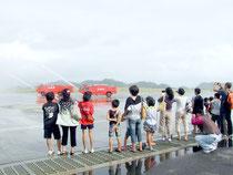 放水を見学する参加者たち=21日午前、新石垣空港