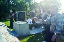 (奥)八重山の戦争被害について説明を受けた=戦争マラリア犠牲者慰霊碑、バンナ公園内。