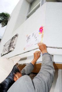 分館の壁に感謝の言葉と風船を貼り付ける大田さん。左にあるのは色あせた分館の看板(31日午後5時ごろ)
