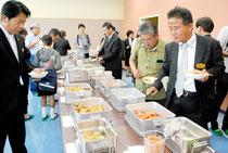 新給食センターで調理した食事を試食する中山市長(左)ら関係者=4日午後、同センター