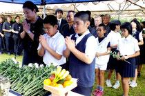 献花し冥福を祈る、児童や一般など市民200人が参列した=市内宮良のタフナー原にある慰霊之塔