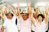 初当選を決め、バンザイ三唱する砂川氏(中央)と支持者=10日夜、選対本部