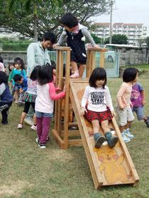 生徒たちの作った木製すべり台を滑る園児たち=22日午前、オリブ保育園