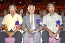 栄誉章を代理で受け、映像「65年の歩み」を見つめる(右から)広晃さん、憲一さん、栄さん=石垣市民会館、浜崎。