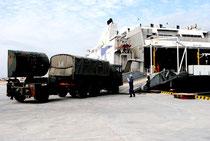 部隊の撤収が始まり、民間の輸送船に搬入される自衛隊の車両=19日午前、新港地区