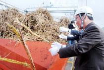 操業開始式でサトウキビをヤードに投げ込む関係者=7日午後、石糖
