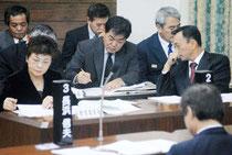 教科書問題を追及する野党に対し、当局と答弁を調整する玉津教育長(右)、石垣委員長=19日、市議会