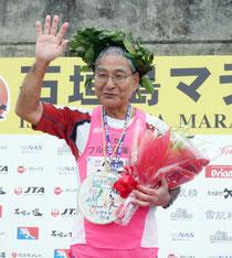 フルマラソン完走100回を達成した上間光明さん=22日午後、陸上競技場