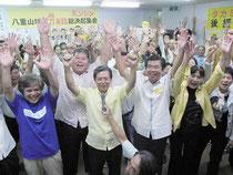 4期目の当選を決めバンザイ三唱する高嶺氏(中央右)と支持者=10日夜、選対本部