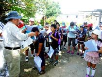 講師の石垣さん(左)の説明を熱心に聞く児童たち=25日午前、美崎御嶽