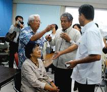 教育委員会終了後、委員に詰め寄る加勢本さん(左)と、割って入る友寄さん(右)=31日午後、市教委