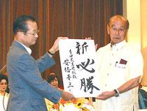 河村氏から安倍首相の為書きを受け取る仲井真氏(27日)