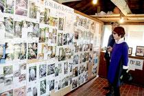 カンムリワシ週間が始まった。「あやぱに写真展」を興味深げに見る観光客=1月31日午後、石垣やいま村
