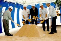 新八重山食肉センターの起工式でくわ入れする関係者=16日午前、大浜の建設予定地