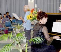 曲の解説を交え「夕やけ」を独唱する田本さんとピアノの玉元さん。観客は静かに耳を傾けていた=大浜公民館