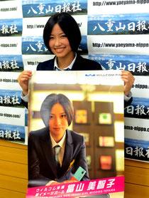 ポスターを手に「沖縄全体を當山ワールドに染めたい」と張り切る當山さん=八重山日報社