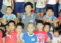 「皆も好きなことを見つけて、頑張ってほしい」と激励し、児童と記念写真を撮る新城選手(中)=登野城小