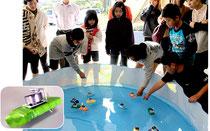 手作りの「ポンポン船」を水槽に浮かべる児童=15日午前、伊野田小学校