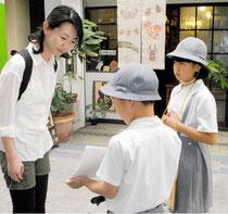 通行人に郷土学習の成果をプレゼンする海星小の児童=18日午後、ユーグレナモール