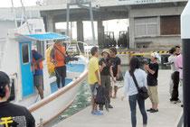石垣島に到着し、取材を受ける「頑張れ!」のツアー参加者(18日午後5時過ぎ)