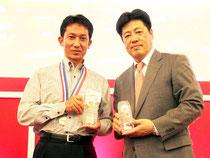 マイスター賞の楯を贈る(右から)楽天トラベルの岡武公士代表と金子さん=グランドプリンスホテル新高輪、東京、9日