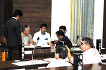 休憩中、答弁の訂正について調整する中山市長(左)と玉津教育長ら。手前右は野党=3日午後、市議会