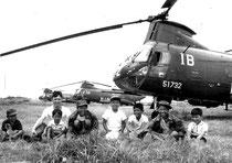 ヘリを背に笑顔の植山さんと子供たち=1972年、石垣空港(モノクロ・植山さん提供)