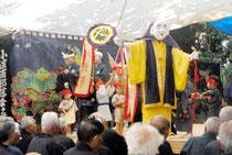 ファーマーを引き連れて舞台に登場した福禄寿=1日午前、竹富町小浜島の嘉保根御嶽