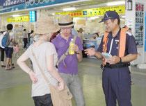 安全推進活動期間中、リーフレットを配布した海保官=2日午前、石垣港離島ターミナル