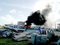 真っ黒な煙を出し燃え上がる廃船、周囲には異臭が漂った=16日、八島町