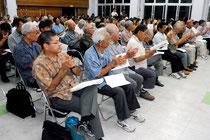 玉津教育長の早期辞任を求める決議を拍手で採択する集会参加者=22日夜、大川公民館