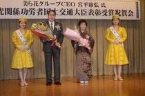 ミス八重山の2人から花束を贈られた宮平さん(中央)と妻の米子さん。関係者が大臣表彰の喜びを分かち合った=ホテルミヤヒラ