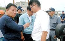 尖閣出港を阻止され、水産庁の職員(右)に説明を求める水島幹事長=7日午後、登野城漁港