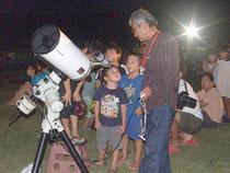 天体望遠鏡で土星を見せてもらう子どもたち