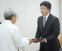 伊是名委員長から当選証書を受け取るトップ当選の平良氏=11日午前、市役所