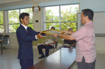 玉津教育長から指定書を受け取る宮良さん(左)=石垣市教育委員会