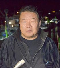 尖閣海域への出港を前に、報道陣のインタビューを受ける水島幹事長=22日夜、石垣漁港