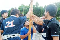 退庁時間後の午後6時ごろ、旗頭を持つ練習に励む職員(26日)