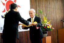 石垣市観光交流協会の50周年記念式典出席のため帰省し、会場で表彰を受ける大浜氏(11月29日)