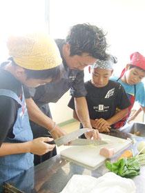 シェフ・原田さんの包丁さばきに、児童たちからは感嘆の声=26日午前、大浜小学校