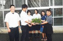 「与那国でバニラを広めて」と、笑顔で請舛さんに苗を手渡す部員=八重山農林高校