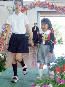 在校生に手を引かれ入場する新1年生の多良間涼香さん(右)=10日午前、平久保小学校