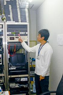警報発信中を示す赤いランプが点灯。Jアラートシステムをチェックする大田さん=FMいしがきサンサンラジオ=大川、午前11時30分。