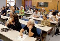 「尖閣問題のカギは歴史」と訴える石井望准教授の話に耳を傾ける聴衆=11日午後、健康福祉センターの視聴覚室