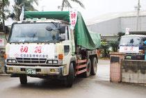 粗糖を満載したトラックが名蔵の製糖工場を出発した=17日午前、石垣島製糖前