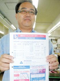 豊見城市役所で市民に提供されている封筒を持つ石垣市職員(17日午後)