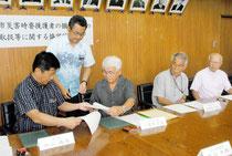 各地域の公民館長たちが見守る中、協定書を交わす中山市長と入嵩西会長=30日午後、市役所