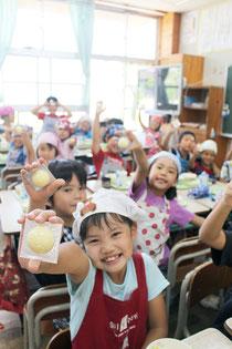 給食に登場したサッカーボール型のチーズに大喜びの八島小学校2年1組の児童=16日午後、同校2年1組の教室