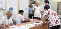 竹富町議選の立候補届け出の受け付けが行われ、候補者の代理人たちが届け出順をくじ引きで決めた=2日午前、町選挙管理委員会