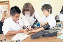 今村さん(中央)から血圧の測り方を教わる高校生たち=26日午後、八重山高校